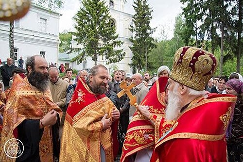о. Віталій Ейсмонт цілує хрест у патріарха Філарета